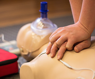 Hands practicing CPR on doll.