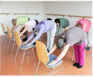 Several women doing stretches on chairs