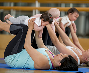 Mothers doing yoga with their babies.
