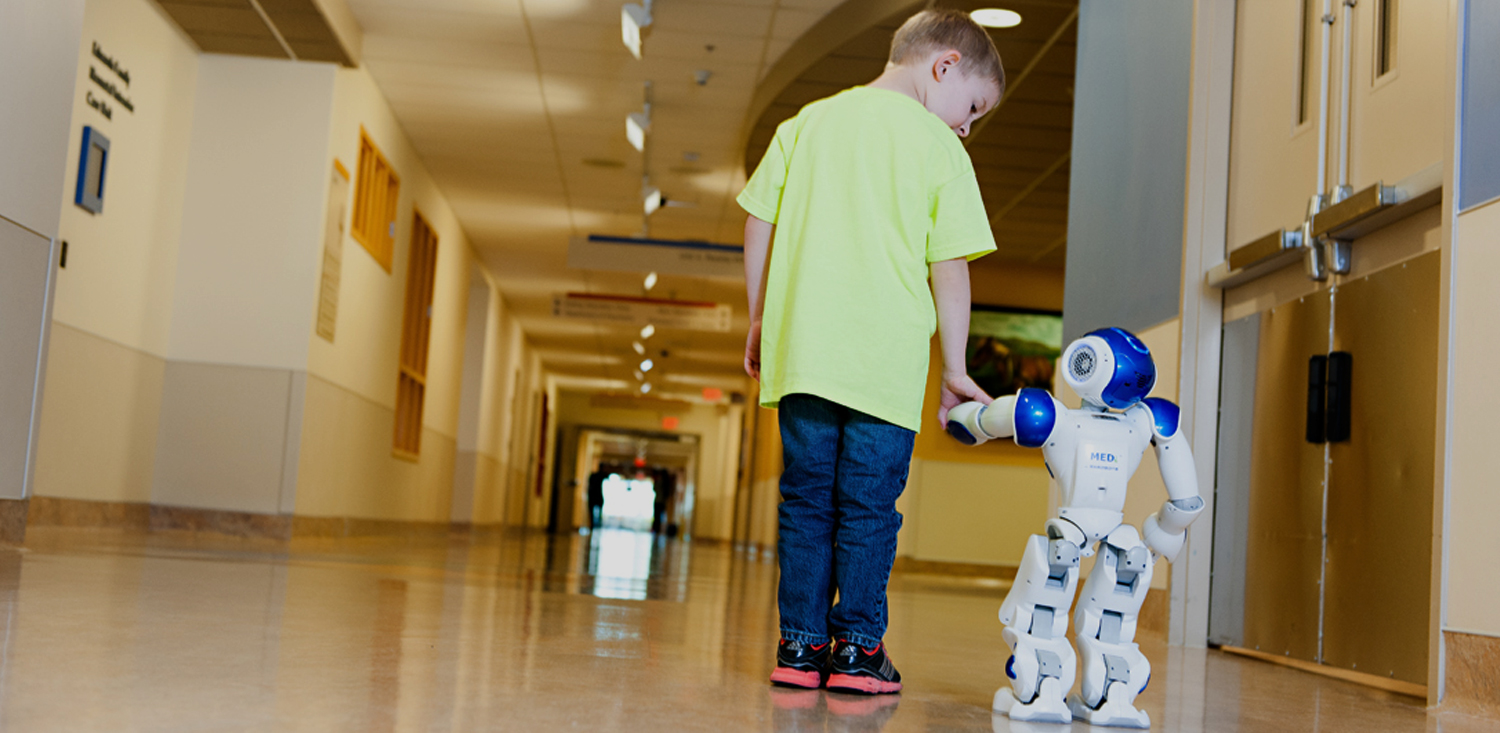 Boy holding hand of MEDI robot at Broward Health